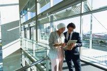 Vue de face des hommes d'affaires travaillant ensemble sur tablette numérique dans le couloir au bureau moderne . — Photo de stock