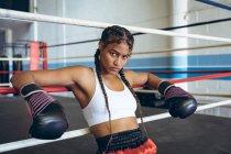 Женщина-боксер в боксёрских перчатках опирается на веревки и смотрит на камеру в боксёрском ринге. Сильная женщина-боец в боксёрском зале тяжело тренируется . — стоковое фото