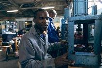 Портрет молодої змішаної раси на фабриці спортивного одягу, яка дивиться на камеру і посміхається з колегами, які працюють на задньому плані. — стокове фото