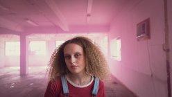 Vue avant d'une jeune femme caucasienne avec le cheveu bouclé regardant intensément à l'appareil-photo tout en restant à l'intérieur d'un entrepôt vide avec le brouillard rose — Photo de stock