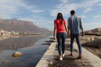 Vista posteriore da vicino di una giovane coppia mista che si tiene per mano camminando su un molo vicino al mare, con cielo blu e montagne sullo sfondo — Foto stock