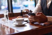 Metà sezione di uomo utilizzando smartphone seduto a un tavolo all'interno di un caffè con una tazza di caffè e un croissant. Nomade digitale in movimento . — Foto stock