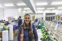 Портрет крупним планом молодий змішаної жінки гонка носіння шарф, стоячи поруч з рядом машин в яскраво освітленій спортивного одягу заводу, дивлячись на камеру і посміхаючись. — стокове фото