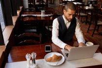 Vista elevada de un joven caucásico usando una computadora portátil sentada en una mesa dentro de un café. Nómada digital en movimiento . - foto de stock