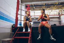 Front view of female boxers talking and wearing hand wrap at boxing club. Strong female fighter in boxing gym training hard. — Stock Photo