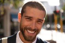 Retrato de perto de um jovem caucasiano sorridente em pé em uma rua ensolarada da cidade. Digital Nomad em movimento . — Fotografia de Stock