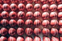 Vista aérea de bolas de cricket rojas en filas al final de la línea de producción en una fábrica . - foto de stock