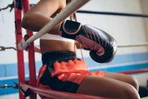 Крупный план женщины-боксера, отдыхающей в боксерском ринге в фитнес-центре. Сильная женщина-боец в боксёрском зале тяжело тренируется . — стоковое фото