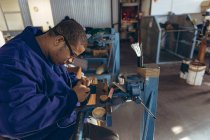 Side view close up of a young African American man wearing glasses standing at a workbench holding thread in his mouth and hands, stitching a ball in a workshop at a factory making cricket balls. — Stock Photo