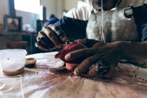 Close up of the hands of man sitting at a workbench stitching red leather shapes at a factory making cricket balls. — Stock Photo