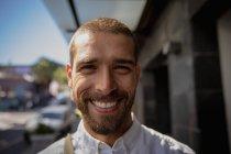 Портрет молодого кавказца на городской улице, улыбающегося в камеру. Цифровая реклама на ходу . — стоковое фото