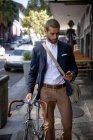 Вид спереду крупним планом молодої кавказької людини, що ходить, використовуючи свій смартфон і велосипеді на міській вулиці. Цифрові кочівники на ходу. — стокове фото