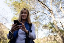 Vista frontale da vicino di una donna caucasica matura che utilizza uno smartphone durante un'escursione — Foto stock