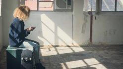 Вид збоку молоді кавказька жінка з Кучеряве волосся за допомогою мобільного телефону поруч з скейтбордом, сидячи всередині порожній склад — стокове фото