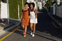 Vista frontal de dos hermanas adultas jóvenes de raza mixta con los brazos alrededor abrazándose mientras caminan en una calle bajo el sol, una con una mochila y la otra con un monopatín - foto de stock