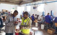 Vue de face d'un jeune manager afro-américain tenant un presse-papiers et parlant avec un jeune travailleur afro-américain dans l'atelier d'une usine de ballon de cricket. Le travailleur tient une balle de cricket . — Photo de stock