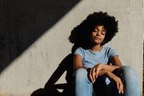 Retrato de perto de uma jovem mulher de raça mista sentada contra uma parede, relaxando com os olhos fechados ao ar livre ao sol — Fotografia de Stock
