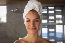 Retrato de perto de uma jovem mulher caucasiana com o cabelo envolto em uma toalha, olhando diretamente para a câmera e sorrindo em um banheiro moderno . — Fotografia de Stock