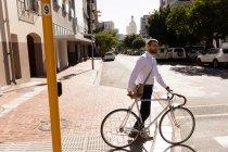 Вид збоку молодого Кавказького чоловіка, що ходить з його велосипедом перетину вулиці в місті. Цифрові кочівники на ходу. — стокове фото