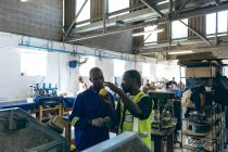 Front view of two young African American male colleagues in discussion beside a machine at a cricket ball factory, one is holding a yellow ball, with people working at machines in the background. — Stock Photo