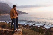 Vue latérale d'un jeune couple mixte debout sur une plage embrassant et regardant vers la mer au coucher du soleil — Photo de stock
