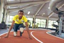 Вид спереди инвалида афроамериканского спортсмена в стартовой позиции на беговой дорожке в фитнес-центре — стоковое фото