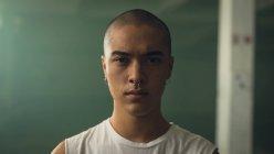 Vista de perto de um jovem hispânico-americano com piercing em ambas as orelhas e nariz vestindo uma mangas brancas enquanto olha atentamente para a câmera — Fotografia de Stock