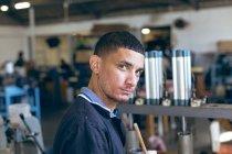 Портрет молодого человека смешанной расы, работающего на заводе спортивного оборудования, поворачивается и смотрит в камеру. — стоковое фото