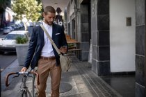 Vista frontal de un joven caucásico caminando, usando su teléfono inteligente y moviendo su bicicleta en una calle de la ciudad. Nómada digital en movimiento . - foto de stock