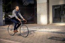 Vista lateral de un joven caucásico montando en bicicleta en una calle de la ciudad. Nómada digital sobre la marcha. - foto de stock