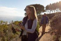 Vista frontal de cerca de una mujer caucásica madura sosteniendo un mapa y una brújula mirando hacia otro lado para orientarse y un hombre usando mochilas caminando solo a lo largo de un sendero durante una caminata . - foto de stock
