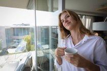 Vue de face gros plan d'une jeune femme caucasienne portant une chemise blanche tenant une tasse de café et souriant . — Photo de stock