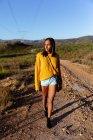 Vista frontale di una giovane donna di razza mista che cammina lungo un sentiero attraverso un paesaggio rurale soleggiato, con montagne all'orizzonte sullo sfondo. Indossa dei pantaloncini, con un top giallo e una borsetta . — Foto stock