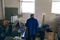 Vista posteriore di un uomo di mezza età che lavora in una fabbrica di attrezzature sportive circondato da macchinari . — Foto stock