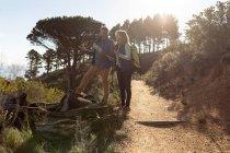 Vue latérale d'une femme et d'un homme caucasiens matures debout et admirant la vue lors d'une randonnée dans la campagne. L'homme tient une carte, ils sont souriants et rétro-éclairés par la lumière du soleil — Photo de stock