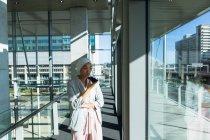 Vista frontal da empresária no hijab olhando pela janela enquanto fala no celular no corredor no escritório . — Fotografia de Stock