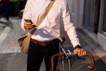 Vista frontal en la mitad de la sección de un hombre usando un teléfono inteligente mientras camina con su bicicleta en la ciudad. Nómada digital sobre la marcha. - foto de stock