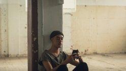Vista laterale di un giovane ispano-americano con piercing che indossa una camicia grigio scuro e berretto seduto mentre utilizza un telefono cellulare all'interno di un magazzino vuoto — Foto stock