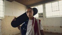 Vista frontal de un joven hispano-americano con una camisa blanca lisa sosteniendo un monopatín negro sobre el hombro y una bandera estadounidense mirando atentamente a la cámara dentro de un almacén vacío - foto de stock