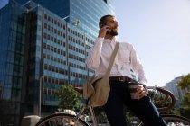 Vista frontale da vicino di un giovane caucasico che tiene in mano un caffè da asporto e parla su uno smartphone, appoggiato sulla sua bicicletta in una strada della città. Nomade digitale in movimento . — Foto stock