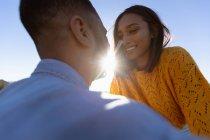 Через плечо вид молодой смешанной расы пара наслаждается придорожный перерыв во время дорожного путешествия. Она сидит на капоте их пикапа, и они улыбаются и собираются поцеловаться. — стоковое фото