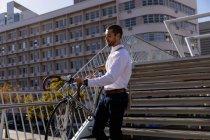Seitenansicht eines jungen kaukasischen Mannes, der sein Fahrrad die Treppe in der Stadt hinunterträgt. Digitaler Nomade unterwegs. — Stockfoto