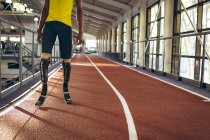 Low section of disabled male athletic standing on running track in fitness center — Stock Photo