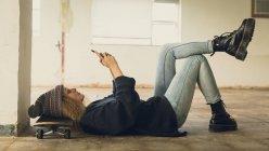 Vista lateral de una joven mujer caucásica con el pelo rizado usando una camisa negra y gorro acostado en el suelo con la cabeza en un monopatín mientras usa un teléfono móvil — Stock Photo