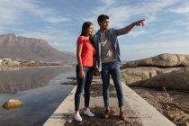 Vista frontale da vicino di una giovane coppia mista che si tiene per mano in piedi su un molo guardando verso il mare, l'uomo sta indicando la distanza — Foto stock