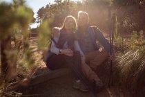 Vista frontal de uma mulher e um homem caucasianos maduros sentados em uma árvore caída juntos segurando bengalas nórdicas e admirando a paisagem durante uma caminhada, iluminados pela luz solar — Fotografia de Stock