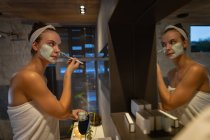 Side view of a young Caucasian woman looking in the mirror and applying a face mask with a brush in a modern bathroom. — Stock Photo