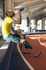 Вид сбоку на инвалида афроамериканского мужчины спортивной питьевой воды на ипподроме в фитнес-центре — стоковое фото