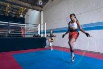 Вид спереди на женщин-боксеров, тренирующихся с скакалкой в боксерском клубе. Сильная женщина-боец в боксёрском зале тяжело тренируется . — стоковое фото