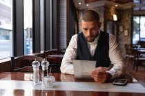 Front view close up of a young Caucasian man sitting at a table in a cafe looking at the menu with his smartphone on the table beside him. Digital Nomad on the go. — Stock Photo
